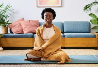 An attractive young Black woman sitting on a yoga mat in her lounge at home meditating.
